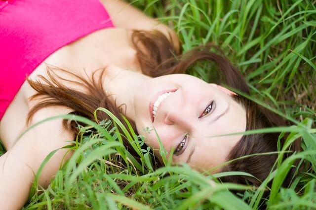 草原に寝そべって微笑む女性
